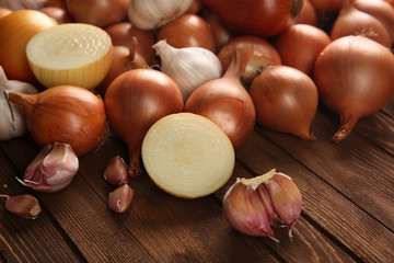 Fresh onions with garlic on wooden background
