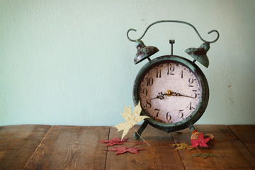 image of vintage alarm clock next to autumn leaves on wooden table in front of wooden background. retro filtered