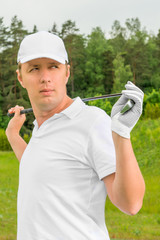 golfer in a white T-shirt and a baseball cap with golf club