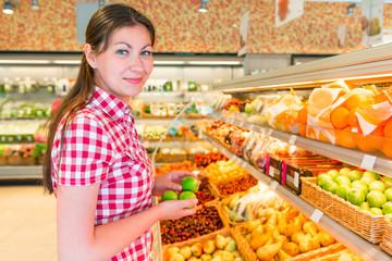 brunette in a supermarket chooses the lemons