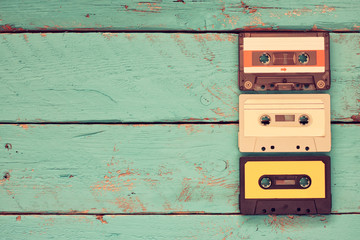 close up photo of vintage cassette tape over aqua wooden table . top view. retro filtered