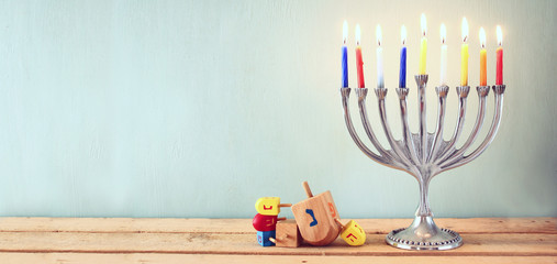 website banner image of of jewish holiday Hanukkah with menorah (traditional Candelabra). retro filtered.