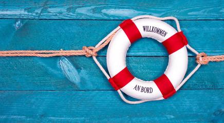 Willkommen an Bord - Rettungsring auf blauem Holz Hintergrund