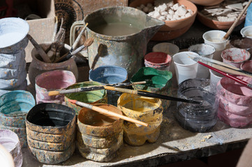 Work table of a pottery decorator of Caltagirone with different color containers and paintbrushes