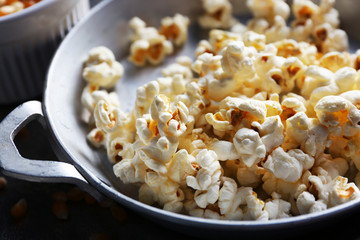 Salted popcorn in a metal bowl with cup of corns on wooden table, close up