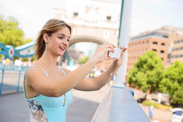 young woman taking a photo from tower bridge with her phone