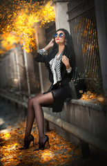 Attractive young woman with sunglasses in autumnal fashion shot. Beautiful lady in black and white outfit with short skirt sitting on wall in park.