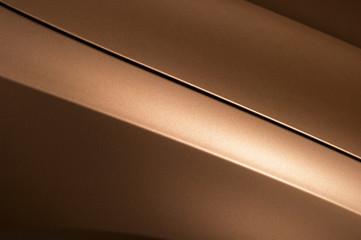 Surface of bronze sport sedan car, detail of metal hood and fender of vehicle bodywork
