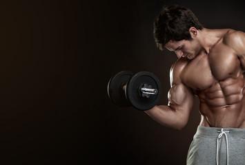 Muscular bodybuilder guy doing exercises with dumbbells over bla