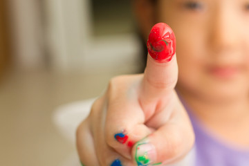 childrent painting red color on her finger