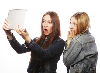 Two pretty young women taking a self portrait with a tablet