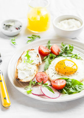 fried egg, fresh vegetable salad and a grilled cheese sandwich on a light plate on white background - healthy Breakfast