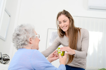 cheerful young girl taking care of old senior woman at home