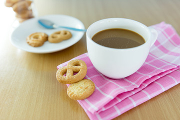 cup of coffee and cookies on wooden