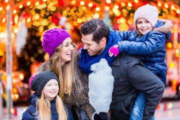 Familie isst Zuckerwatte auf Weihnachtsmarkt an Weihnachten