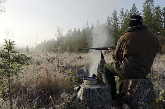 Moose hunter sitting on a stump with a litle smoky fire in front holding a rifle , picture from the North of Sweden.