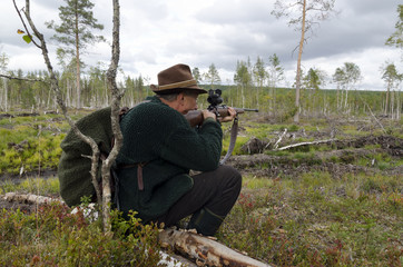 Moose hunter sitting on a stump aiming with a rifle, picture from the North of Sweden.