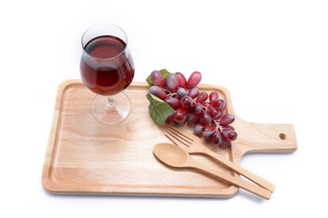 Red wine and grapes on a wooden floor.