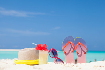 colourful picture of flip flops, sun hat, pina colada cocktail with hibiscus and pink sunglasses near the beach