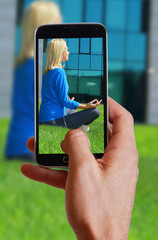 Male hand taking photo of Woman  meditating  in  City Central Park in yoga lotus pose with cell, mobile phone. Sport, fitness, active lifestyle , urban workout concept