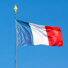 Squared shot of the flag of France on a pole, waving in the wind during a sunny day with clear blue sky.