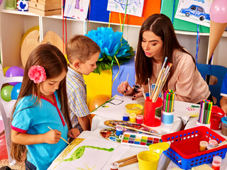 Children with teacher woman painting on paper in  kindergarten