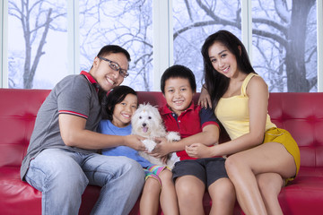Beautiful family sitting on sofa with puppy