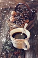 Ñup of coffee, pine cones, walnuts and cinnamon sticks and snowf