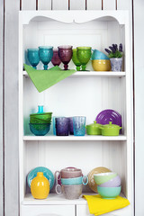 Clean glasses, plates and cutlery on shelves in kitchen cupboard