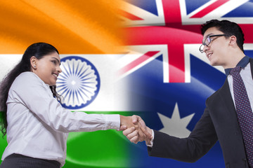Indian woman shaking hands with Australian person