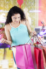 Woman opens shopping bags at the mall