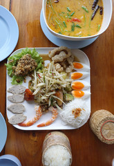 Spicy papaya salad serving with shrimp, boiled egg, porkball and