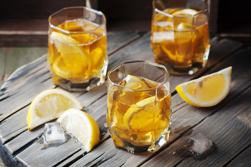 Cold whiskey with ice and lemon on the vintage table