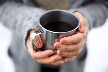 Hand holding coffee cup, outdoors