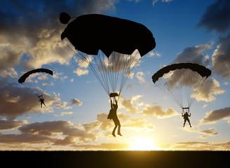 Foto op Aluminium Luchtsport Silhouette skydiver parachutist landing at sunset