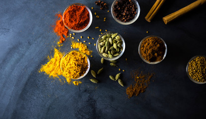 Closeup of various colorful spices bowl and spoon on dark granite table