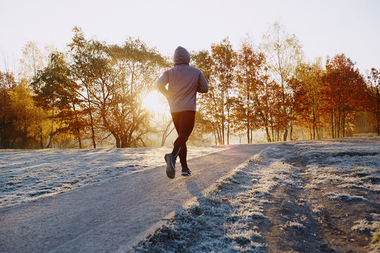 Young man running at park during cold autumn morning.