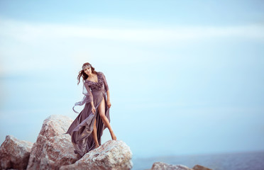 Beautiful Girl In A Fairy Purple Long Dress On A Stones