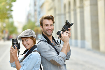 Trendy photographers with camera standing in the street