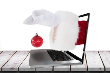 Composite image of santa claus holding red bauble