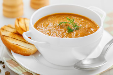 Lentil cream soup with toasts on white table