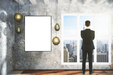 Businessman and blank picture frame and lamps  on concrete wall
