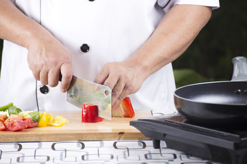 Chef cutting red bell pepper