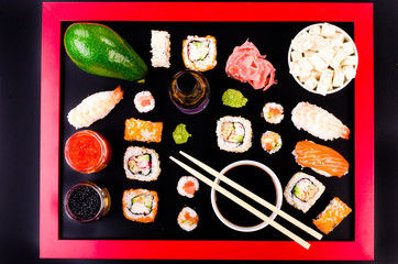 Sushi set, soy cheese, lime, ginger, avocado,  red caviar, black caviar,  soy sauce, wasabi on black background with red frame