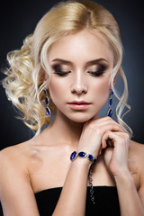 Beautiful blond girl in a black dress with evening haircut  form of waves and bright makeup. Beauty face