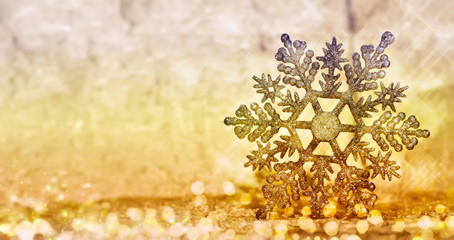 Christmas glowing golden snowflake on blurred background.