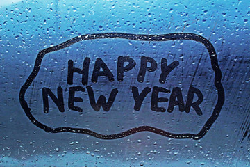 """The inscription """"happy new year"""" on the misted window"""