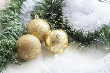 Gold decorative Christmas ball and green and white garland on white background