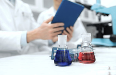 close up of scientists with flasks and tablet pc