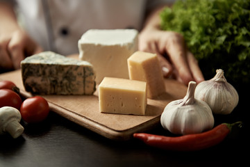Collection of cheese on wooden board. Male chef holding tray with various cheese types.